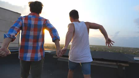 hoşgörü : Friends rejoices life during standing on roof at sunset time. Gay couple raising hands showing joyful emotions. Men standing rooftop and victoriously outstretching arms up. Beautiful view. Slow motion Stok Video