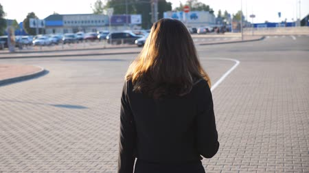 área de trabalho : Young businesswoman walking at street near auto parking at sunny day. Business woman going to work. Unrecognizable girl being on his way to office. Rear Back view Slow motion Close up