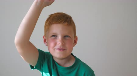 freckles : Handsome cute kid dancing with raising hands indoor. Happy male child closing his eyes and enjoy to rejoicing achievement. Portrait of red-haired boy with freckles having fun inside. Slow motion