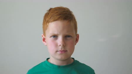 saçlı : Portrait of young serious red-haired boy with freckles inside. Adorable handsome kid looking into camera indoor. Close up emotions of little male child with sad expression on face. Slow motion