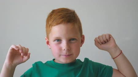 グラブ : Handsome red-haired boy with freckles looking into camera and raise hands rejoicing achievement inside. Portrait of happy young child grabbing his head and showing joy on his face. Slow motion