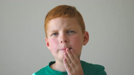 freckles : Young kid looking at camera and touch his face expressing a desperate. Portrait of serious red-haired boy with freckles indoor. Close up emotions of male child with sad expression. Slow motion