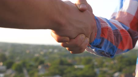 together trust : Two friends meeting on rooftop and greeting each other. Young men shaking hands on blurred cityscape background. Friendly handshake between guys outdoor. Concept of friendship. Close up Slow motion Stock Footage