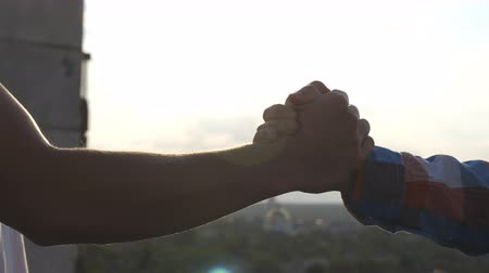symbol of respect : Close up of two friends meeting on rooftop and having a firm friendly handshake outdoor. Young men greeting each other and shaking hands on cityscape background. Concept of friendship. Slow motion Stock Footage