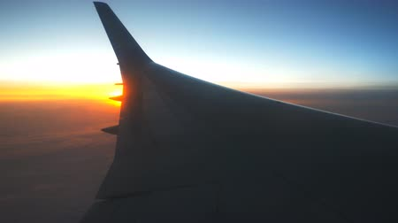 aeroespaço : View from airplane window to sunrise or sunset. Wing of plane flying above the clouds with sun light. Aircraft flight at sky. Concept of traveling by air. Trip by airliner with beautiful background