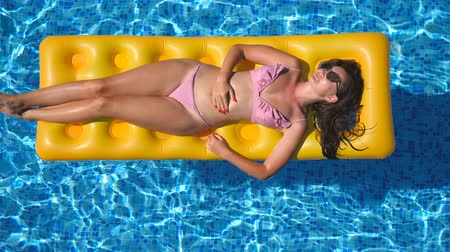 матрац : Beautiful girl in sunglasses and bikini lying on yellow inflatable mattress in swimming pool. Young tanned woman relaxing in basin of hotel on sunny day. Concept of summer vacation. Top view Close up