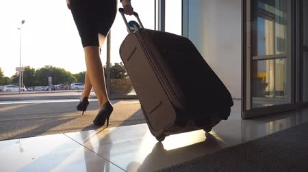 concourse : Business lady leaving airport through automatic glass door with her luggage. Young woman in heels walking from terminal and roll suitcase on wheels. Concept of work trip or travel. Slow motion