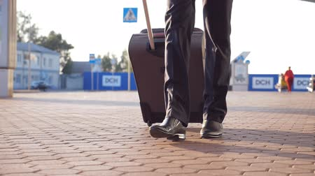 bavul : Close up of feet of successful businessman walking near terminal and pulling suitcase on wheels. Legs of young male business person going with his luggage from airport after flight. Slow motion