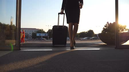 concourse : Business lady going to the airport with her luggage. Young woman in heels entering walking through glass doors to the terminal and roll suitcase on wheels. Trip or vacation travel concept. Slow motion