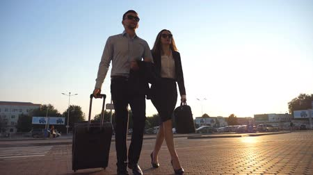 valigetta : Businessman with his female colleague walking at the city street and roll suitcase on wheels. Business man and woman stepping to the office building or airport terminal. Travel concept. Slow motion