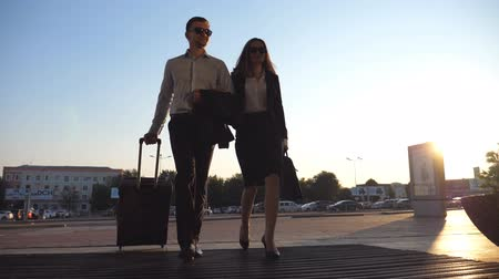valigetta : Businessman with his female colleague walking through enter to terminal and roll suitcase on wheels. Business man and woman stepping to the airport or office building together. Slow motion Close up