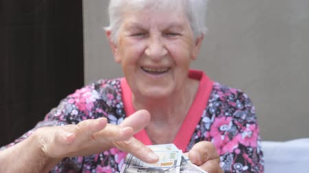 scatters : Happy grandmother holding bundle of money in hands and scattering foreign currency on the desk. Portrait of old smiling woman throwing one hundred dollar bills on the table. Close up Slow motion