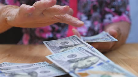 feixes : Grandmother holding bundle of money in hands and scattering foreign currency on the desk. Arms of old woman throwing one hundred dollar bills on the table in front to camera. Close up Slow motion Stock Footage