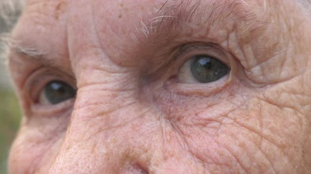 smutny : Close up gray eyes of elderly woman with wrinkles around them. Portrait of grandmother looking into camera with a sad sight. Sorrow facial expression of senior lady