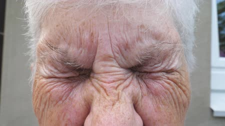 yüz buruşturma : Close up wrinkled face of old grandmother looking into camera with a sad sight. Portrait of mature woman strongly screwing up her gray eyes. Sorrow facial expression of senior lady. Slow motion
