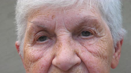 smutny : Close up gray eyes of grandmother with wrinkles around them. Portrait of senior lady looking into the distance with a sad sight. Sorrow facial expression of elderly woman Wideo