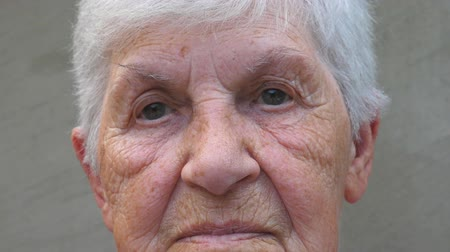 smutny : Portrait of old grandmother with a sad sight. Wrinkled face of elderly lady looking into camera. Sorrow facial expression of granny. Close up gaze of mature woman Wideo