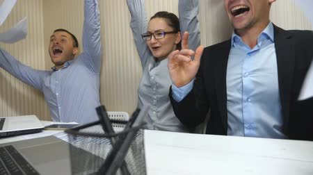 zasedací místnost : Young business people celebrating achievement throwing up documents and showing joyful emotions. Office workers rejoicing success after hard work. Creative team working at modern office. Slow motion Dostupné videozáznamy