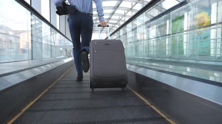 держит : Legs of successful businessman running in hall of terminal and pulling suitcase on wheels. Camera follow to young man with his luggage is late for flight. Guy hurry to business trip. Slow motion
