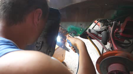 kaynakçı : Male repairman or mechanic worker welds metal parts of old car with welding machine in garage. Adult welder doing welds work using professional equipment and protective mask in workshop. Close up Stok Video