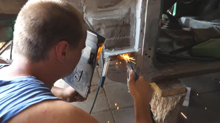 kaynakçı : Male automaster welds metal parts of old car with welding machine in garage. Adult repairman or mechanic worker doing welds work using professional equipment and protective mask indoor. Dolly shot
