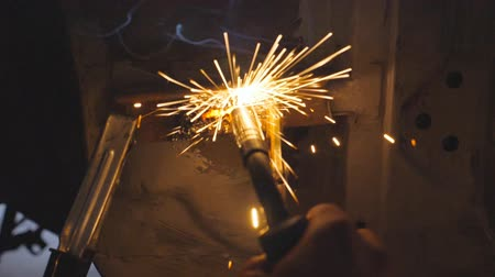 kaynakçı : Close up male hand of professional repairman or mechanic worker welds metal parts of old car using welding machine in garage. Flashes and sparks flies from welding work at dark in workshop