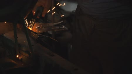 kaynakçı : Male hand of repairman or mechanic worker welds metal parts of old car using welding machine in workshop. Flashes and sparks flies from welding work at dark in garage. Close up Slow motion Dolly shot Stok Video