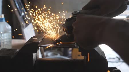 сварщик : Close up arms of male welder sawing metal with a circular saw in garage. Male hands of professional repairman or mechanic worker cutting steel using electric grinding wheel in workshop. Dolly shot