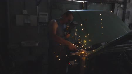 kaynakçı : Professional repairman or mechanic worker welds metal parts of old car using welding machine and protective mask in workshop. Flashes and sparks flying from welding work at dark in garage. Crane shot Stok Video