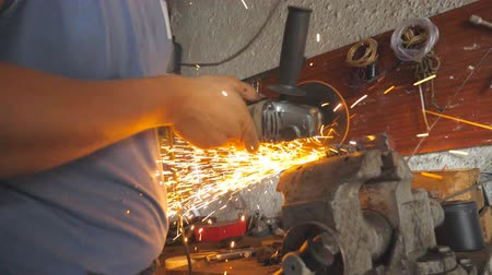 kaynakçı : Arms of professional repairman or mechanic worker sawing metal with a circular saw in garage. Male hands of adult welder cutting steel using electric grinding wheel in workshop. Dolly shot Slow motion
