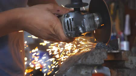 kaynakçı : Close up male hands of adult welder cutting steel using electric grinding wheel in workshop. Arms of professional repairman or mechanic worker sawing metal with a circular saw in garage. Slow motion