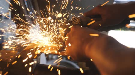 kaynakçı : Male hands of male welder cutting steel using electric grinding wheel in workshop. Arms of professional repairman or mechanic worker sawing metal with a circular saw in garage. Side view Close up