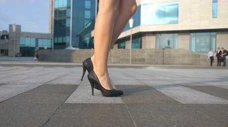 emancipation : Female legs in high heels shoes walking in the urban street. Feet of young business woman in high-heeled footwear going in the city. Girl stepping to work. Slow motion Close up