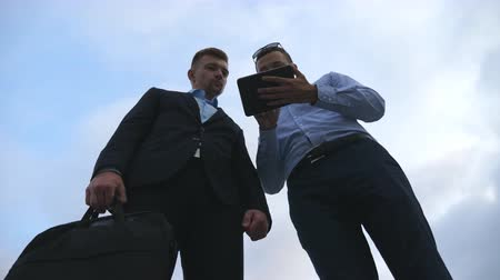 consultancy : Two young businessmen talking and using tablet pc outdoor. Business men working on digital tablet outside with sky at background. Colleagues applying mobile technology. Low angle of view Slow motion