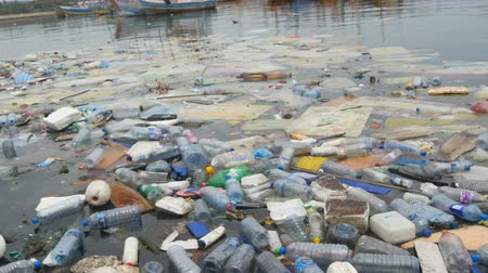 produtos químicos : Environmental pollution. Plastic bottles, bags, trash in river, lake. Rubbish and pollution floating in water
