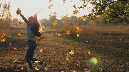 lombhullató : Young woman raising her hands and spinning around scattering autumn leaves. Happy girl showing joyful emotions with sunset at background. Lady enjoying beautiful autumn environment. Slow mo Close up