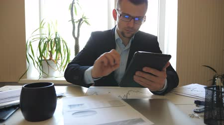 メモ帳 : Serious businessman in eyeglasses looking at diagrams with statistics on papers while working on digital device. Successful entrepreneur analyzing statistical data information on a tablet pc in office 動画素材