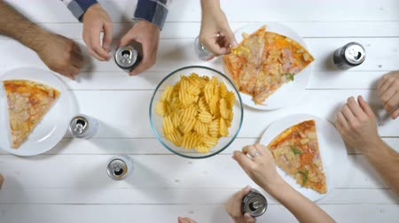 drink cans : Close up male and female hands drinking cola from aluminum cans on wooden table background. Group of best friends sitting at the desk and eating snacks during meeting indoor. Top view Slow motion Stock Footage
