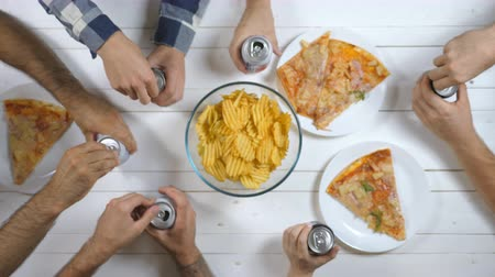 drink cans : Top view male and female hands opening and clicking aluminum cans with soda on wooden table background. Group of best friends sitting at the desk and toasting together with cola indoor. Slow motion