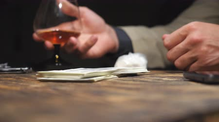 pálinka : Male hands of customer putting a bundle of foreign currency on the table. Arms of drug dealer taking money, giving cocaine for customer and shaking hands for each other. Close up Slow motion