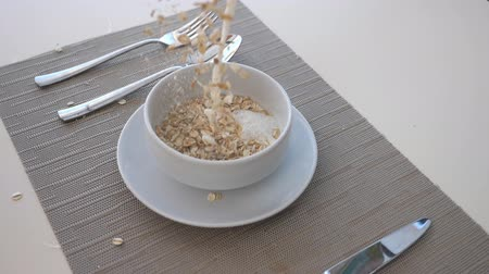 flocos de milho : Detail view on dry crispy cereal and milk pouring into bowl. Close up of bowl with healthy breakfast and cutlery on table. Healthy food concept. Slow motion Stock Footage