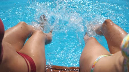 dangle : Female legs splashing crystal clear water in pool of hotel. Two friends sitting on edge of basin and enjoying their vacation at sunny day. Concept of summer vacation or holiday. Slow mo Point of view
