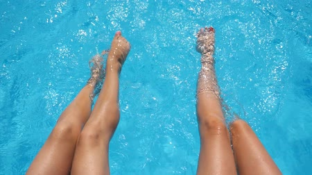 dangle : Top view on female legs splashing crystal clear water in pool of hotel. Two friends sitting on edge of basin and enjoying their vacation at sunny day. Concept of summer vacation or holiday. Slow mo Stock Footage