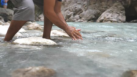 corrente : Unrecognizable man washing his hands in mountain river with clear cool water. Guy standing among river with fast stream and refreshing. Male hiker during his travelling. Slow mo Bottom view Close up Vídeos