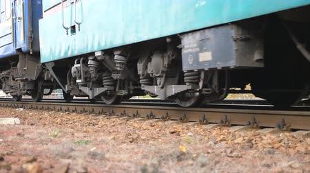 chegar : Close up spinning steel wheels of the train moving along the rail track. Passenger railway transport passing by a camera. Concept of transportation and travel. Low angle view Slow motion