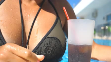 закалки : Young sexy girl quenching thirst with cool drink while swimming in hot sunny day. Attractive tanned woman floating in basin of hotel and enjoying resting on resort. Slow motion Close up