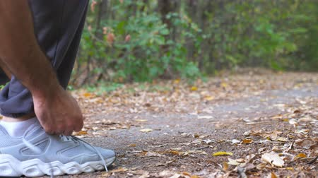 cipőfűző : Close up of young sportsman ties shoe in early autumn forest. Athlete tying shoelaces on sneakers before jogging during training outdoor. Feet of strong man jogging along path at nature. Low view Stock mozgókép