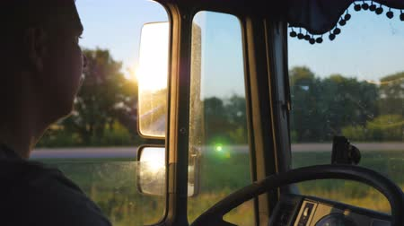 semi profile : Man driving truck and carefully watching the road. Caucasian guy is riding through countryside with beautiful landscape at background. Profile of lorry driver inside the cab. Slow motion Close up Stock Footage
