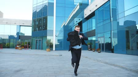 aktatáska : Young businessman with briefcase runs and looks at his watch. Confident guy late for meeting. Successful man in suit jogging near modern building. Handsome man in hurry to appointment. Slow motion Stock mozgókép