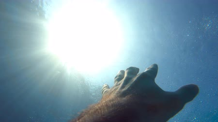 sos : Male hand stretches from under the water to sunrays. Arm asking for help and trying to reach to the sun. Point of view of man drowning in the sea or ocean and floating to the surface. Slow motion POV Stok Video